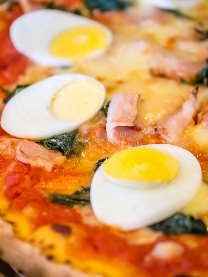 Boiled egg topped pizza. Closeup shot of boiled egg topped homemade pizza royalty free stock photography