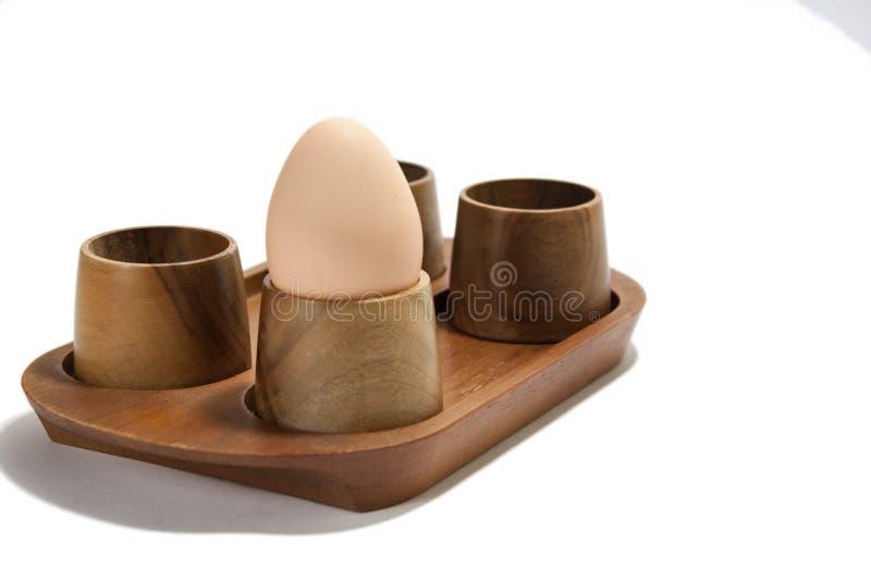 Boiled egg in the wooden holder stock photo