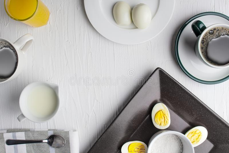 Boiled eggs on a brown plate with coffee, cream and orange juice and salt. Boiled eggs from a chicken, cooked with their shells unbroken, immersion in boiling royalty free stock photos
