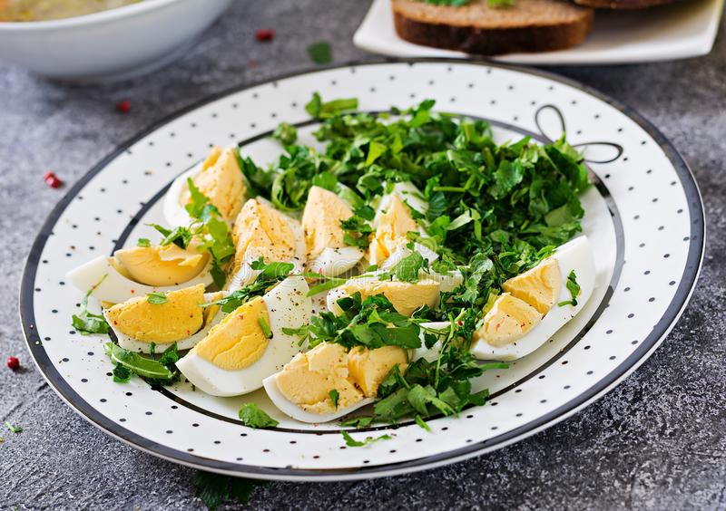 Boiled eggs with greens. Healthy food. Summer salad. Grey bsckground stock photos