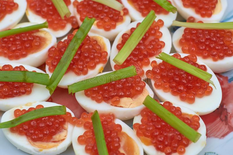 Boiled eggs with red caviar and green onions stock photo