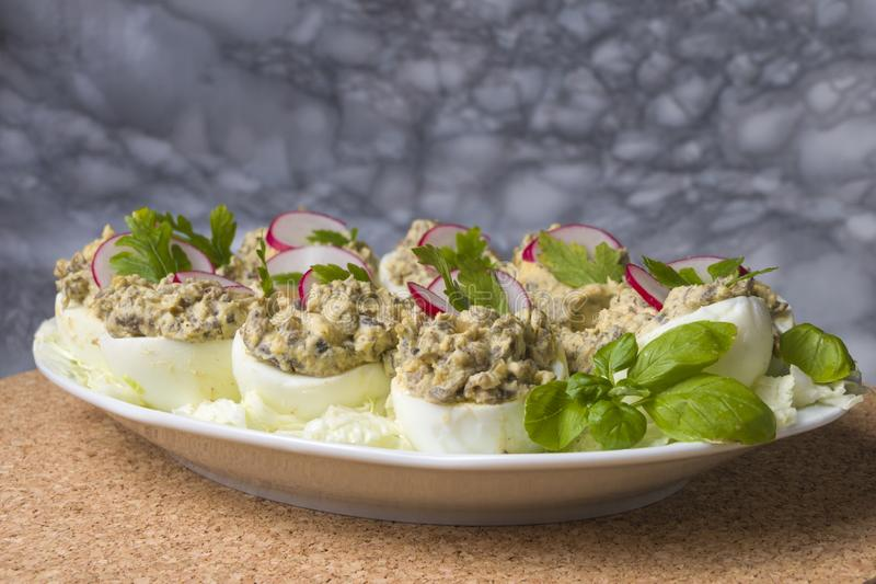Boiled eggs stuffed with champignon mushrooms and sliced radish, parsley, salad on white plate stock photos