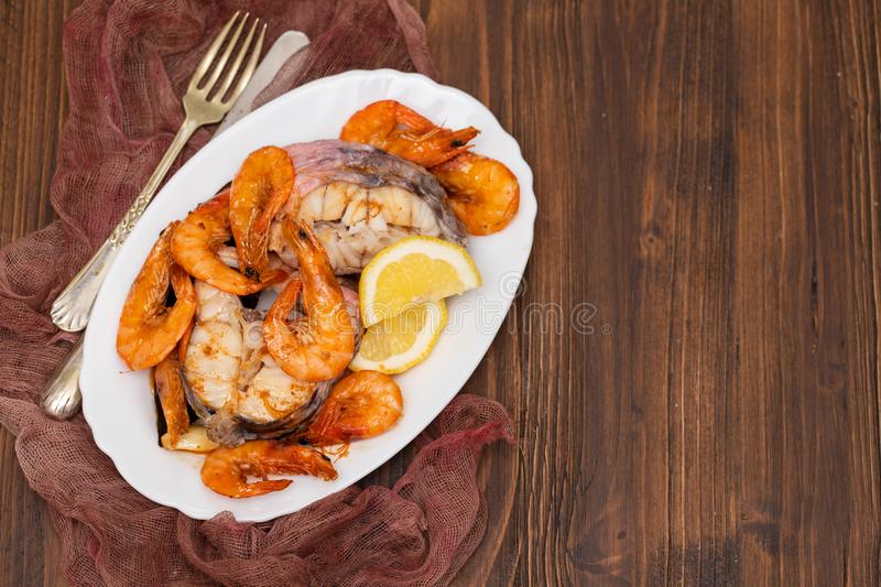 Boiled fish with shrimps and lemon on white dish. On brown wooden background royalty free stock photos