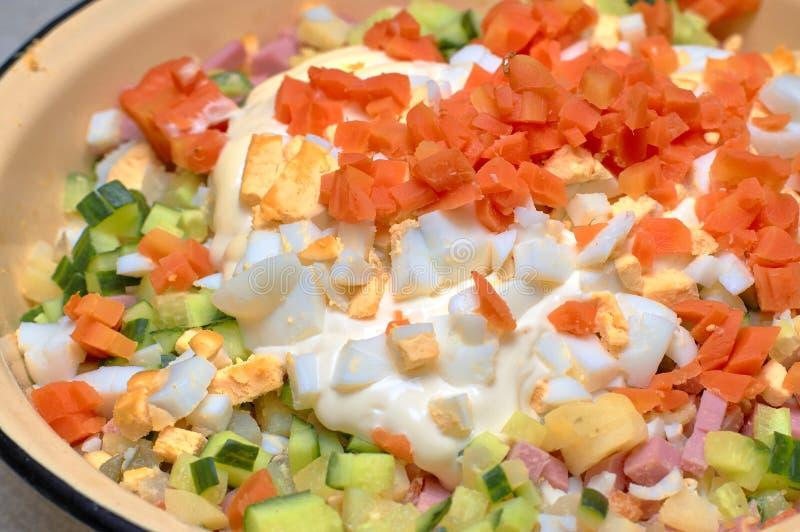 Boiled ha tagliato le carote a pezzi ? versata sopra gli ingredienti tagliati quando cucina l'insalata russa fotografia stock