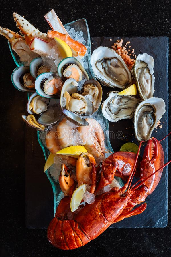 Boiled lobster, fresh oysters, shrimps, mussels and clams served in black stone plate.  royalty free stock image