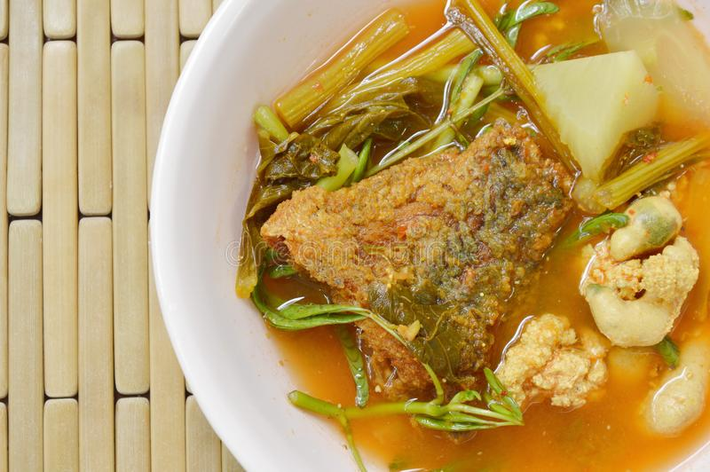 Boiled mixed vegetable topping fried fish and egg in Thai spicy soup on bowl. Boiled mixed vegetable topping fried fish and egg in Thai spicy soup on the bowl stock image