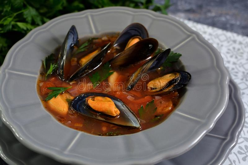 Boiled mussels soup on a grey plate stock images