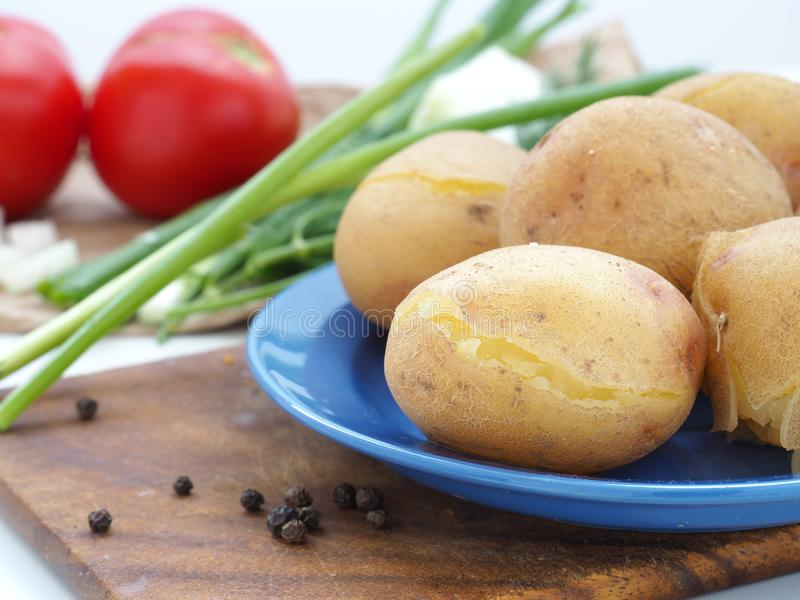 Boiled potatoes in blue dish stock photos