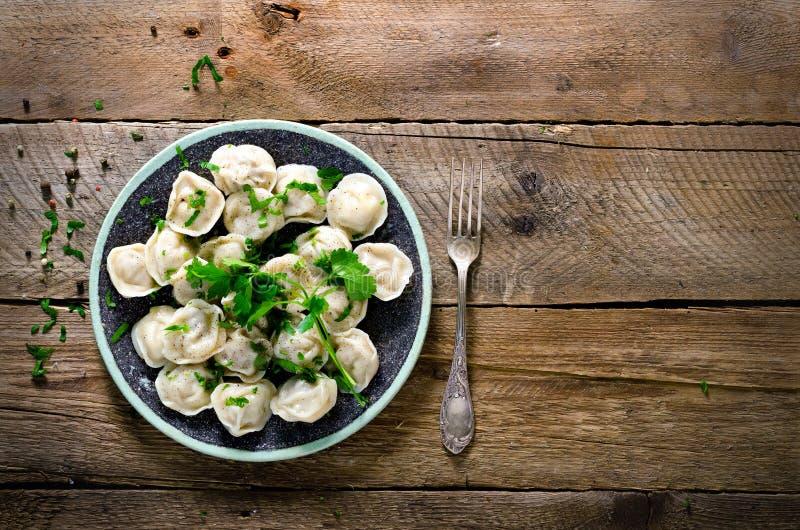 Boiled a préparé le pelmeni russe fait maison, les boulettes, ravioli avec de la viande du plat gris avec le persil frais, poivre photos libres de droits