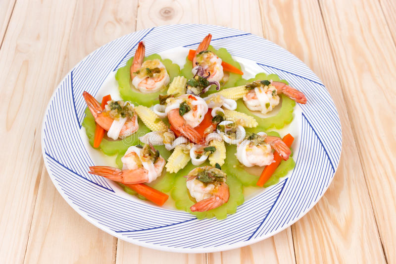 Boiled shrimp, squid and vegetable topping with spicy seafood sauce. On wooden background royalty free stock images