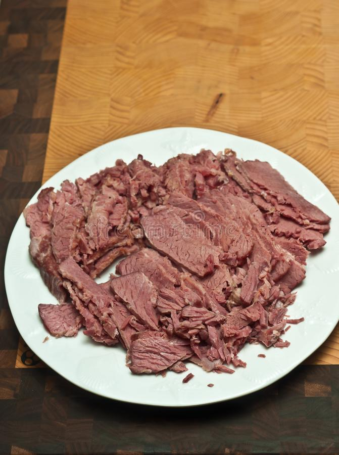 Boiled, sliced, corn beef brisket, on a round, white plate,non a bamboo, wood, cutting board stock photo