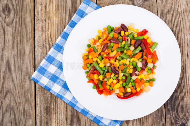 Boiled vegetables in white plate on old wooden table. Healthy vegetarian or vegan food. Closeup royalty free stock photography