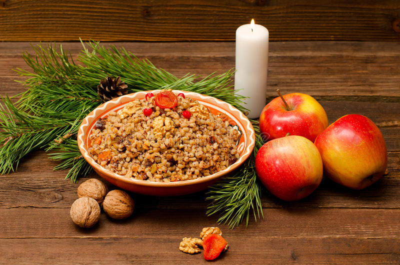 Boiled wheat - a traditional Christmas treat of the Slavs on Christmas Eve kutia. Fur-tree branch, apple, candle on a wooden backg. Round stock images