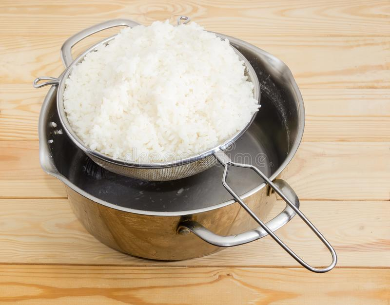 Boiled white rice in stainless steel sieve over stock pot. Boiled and washed white rice in the round stainless steel sieve on stainless steel stock pot on a royalty free stock images
