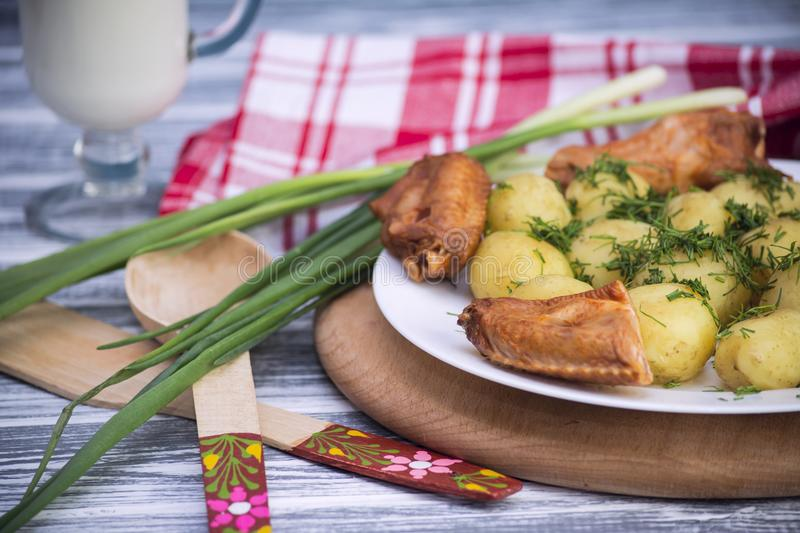 Boiled young potato with smoked chicken wings royalty free stock photos