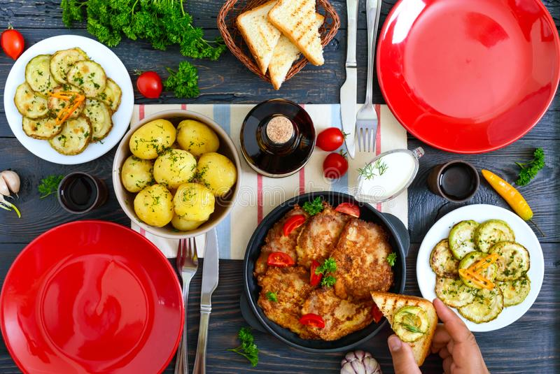 Boiled young potatoes, fried zucchini slices, schnitzels on a wooden table. Top view. Served table for family dinner, lunch. stock images