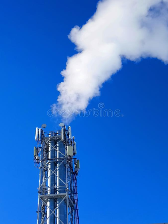 Boiler pipes with smoke on the blue sky background royalty free stock photography