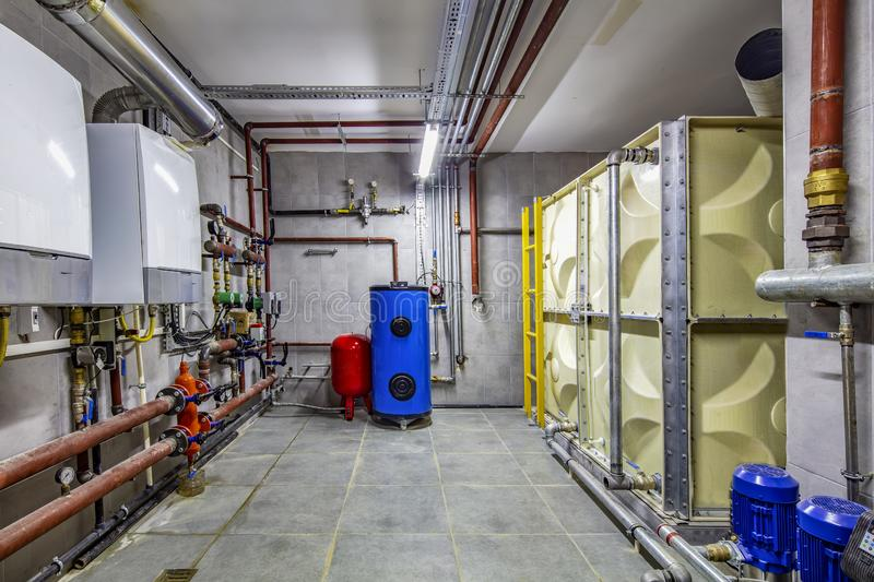 Boiler room; these pipes are for industry heating with an expansion vessel for absorbing pressure difference. Boiler room under construction and installation stock photos
