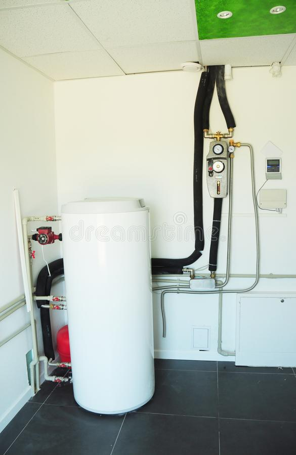 Boiler room with solar water heater tank for house energy efficiency. Modern gas boiler, heating electric warm water system stock photography