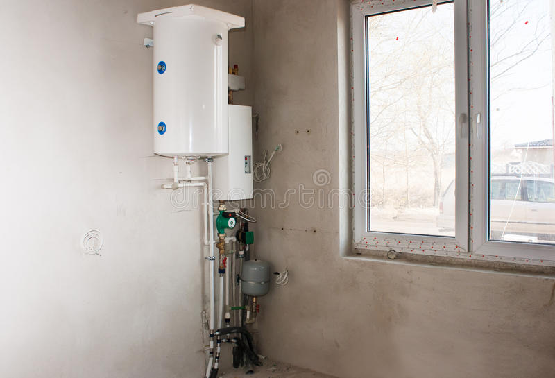 Boiler with system of heating tubes. White boiler with system of heating tubes on the wall in the room of new house royalty free stock photography
