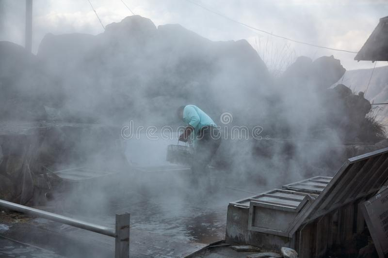 Preparing of black eggs in the hot springs of the volcanic valley, Owakudani. Hakone. Honshu. Japan. Boiling of black eggs Kuro tamago in the sulfur water of hot stock images