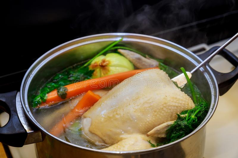 Boiling chicken broth with vegetables in steel pot on gas stove top royalty free stock photo