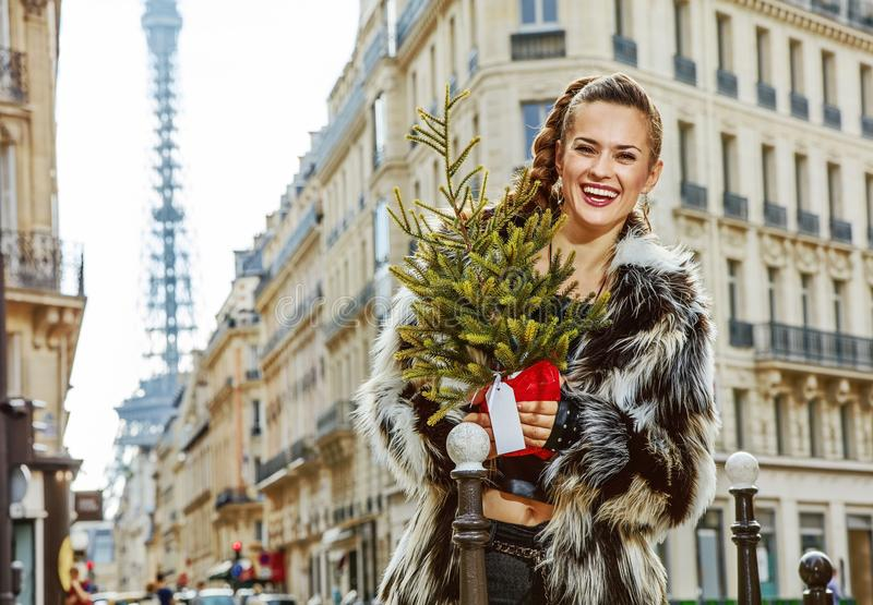 Happy modern woman with Christmas tree in Paris, France. Boiling hot trendy winter in Paris. Portrait of happy modern woman with Christmas tree in Paris, France royalty free stock photo