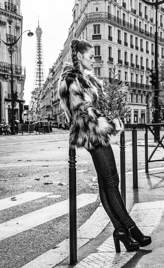 Relaxed trendy woman with Christmas tree in Paris, France. Boiling hot trendy winter in Paris. Portrait of relaxed trendy woman with Christmas tree in Paris royalty free stock images