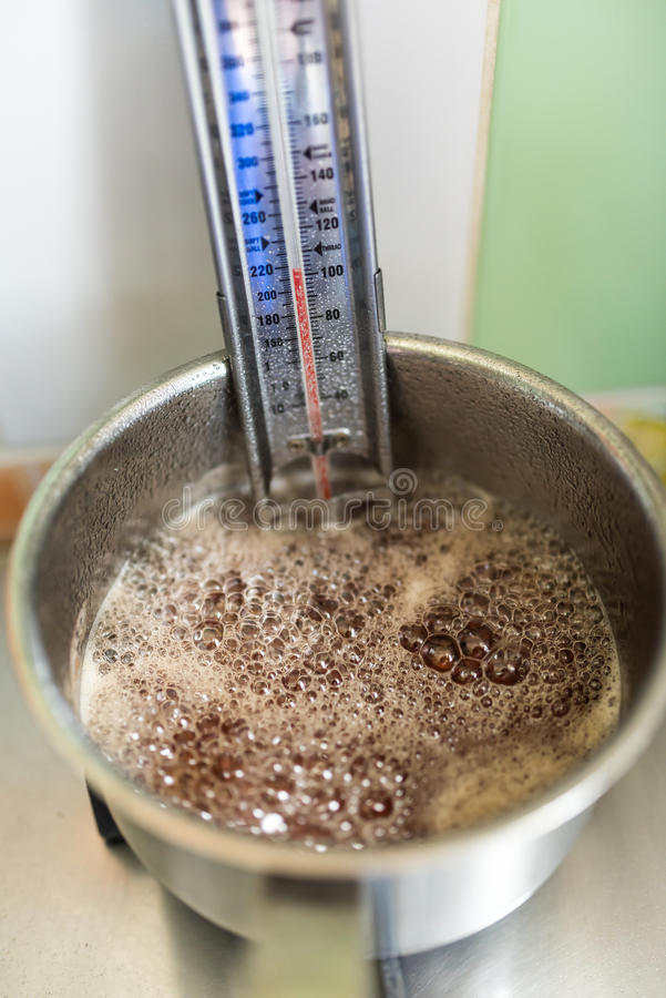Boiling lilac jelly. Lilac jelly- preparation step, boiling with candy thermometer stock photos