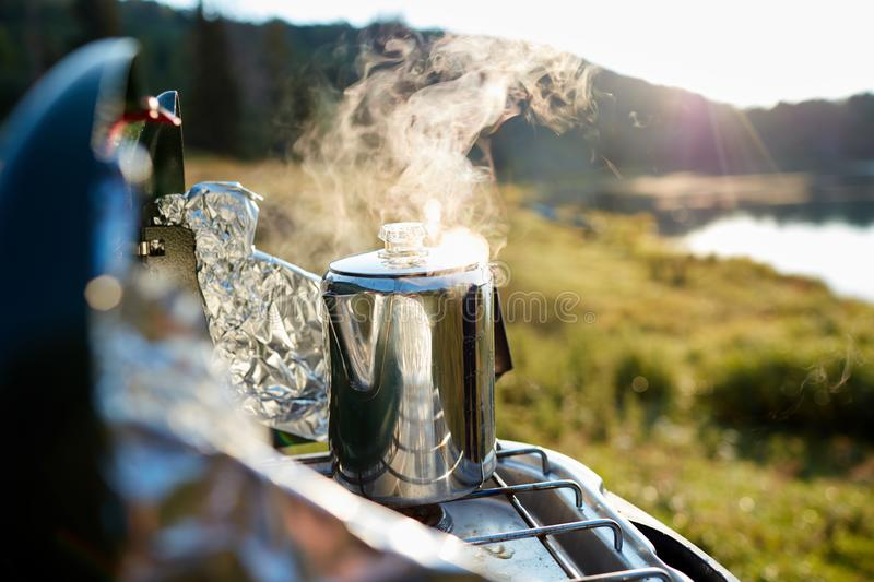 Boiling metal coffee pot on a gas burner. With clouds of steam in early morning light overlooking a tranquil lake stock photography