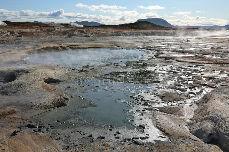 Boiling mud pots in Hverir Namafjall geothermal place in Iceland. Boiling mud pots surrounded by sulfur hot springs in Hverir Namafjall geothermal place in royalty free stock photos