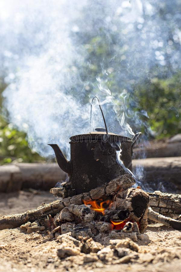 Boiling, sooty kettle with hot drink stands on a campfire in the smoke, in a forest. stock photo