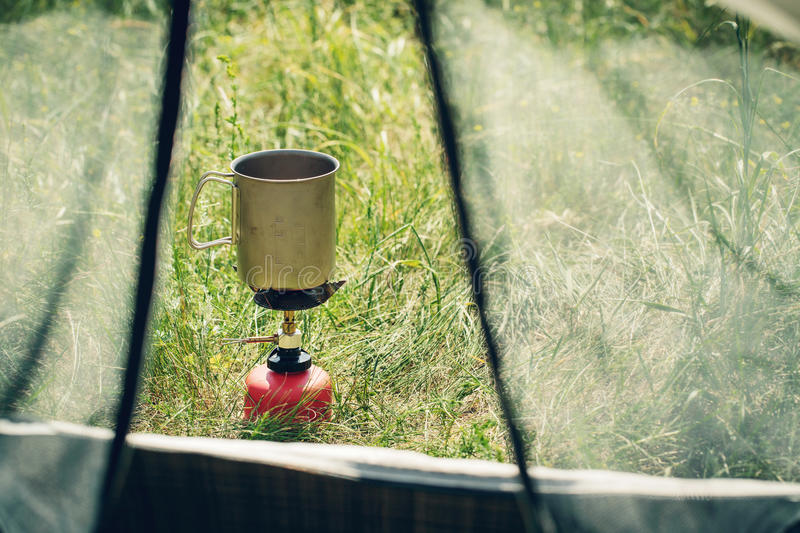 Boiling water in mug on portable camping stove stock image