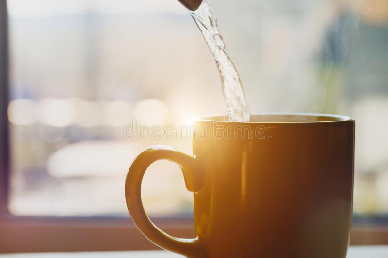 Boiling water pouring into a cup from kettle, making morning coffee. Sunlight royalty free stock photo