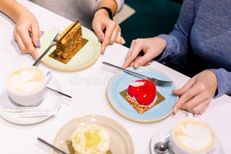 Boire du café et manger ensemble des desserts. Vue du haut des mains de deux belles femmes tenant la main sur des assiettes avec photo stock