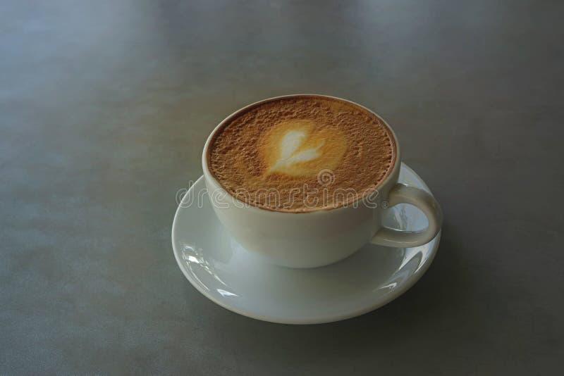Boire savoureux, une tasse de café de capuccino décorée du modèle de coeur sur la mousse brune de lait dans la tasse en céramique photo libre de droits