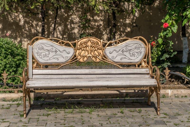Bois antique et banc décoré métallique à un parc Ornements décorés d'or photos libres de droits