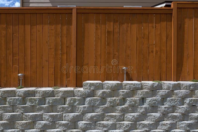 Bois clôturant sur le mur de soutènement en pierre de pile de ciment photos libres de droits