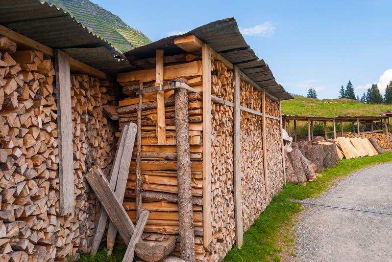 Bois coupé empilé dans un tas de bois et préparé pour chauffer en hiver La Suisse alpestre images stock