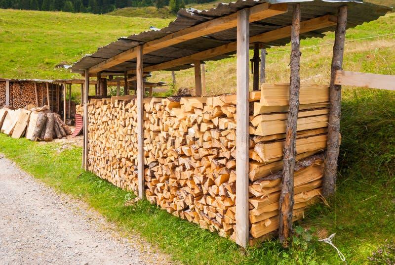 Bois coupé empilé dans un tas de bois et préparé pour chauffer en hiver La Suisse alpestre photos stock