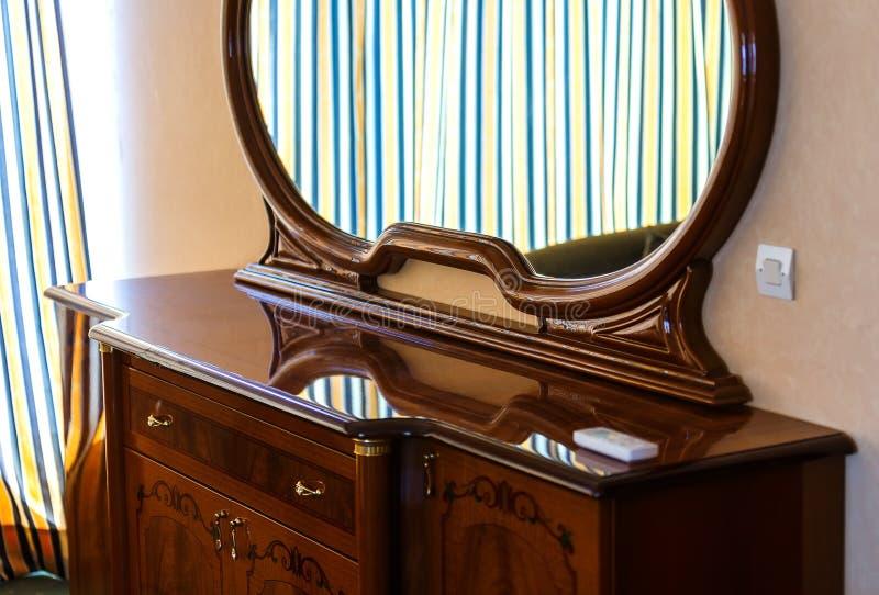 Bois de brun de miroir de vintage de plan rapproché sur la raboteuse dans la tache floue de la chambre photo stock