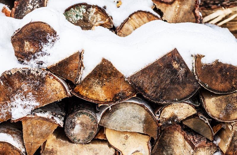 Bois de chauffage coupé empilé couvert par la neige en hiver images stock