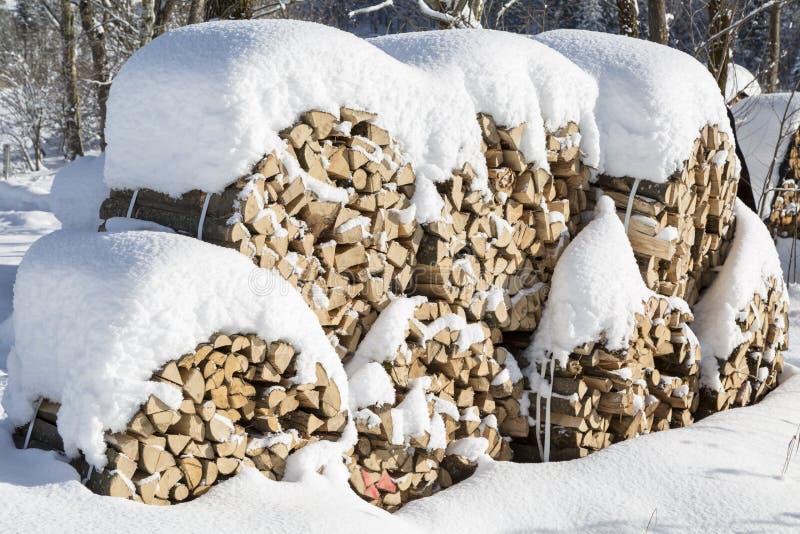 Bois de chauffage coupé empilé couvert par la neige en hiver image libre de droits