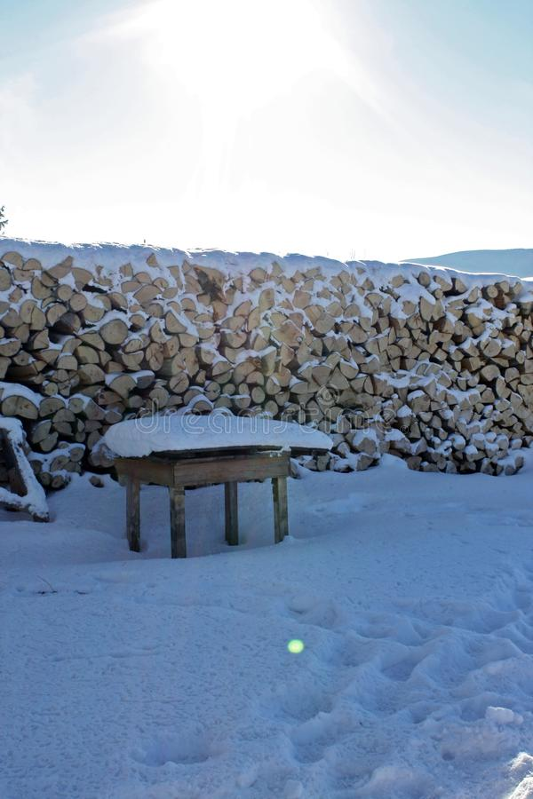 Bois de chauffage empilé dehors dans la neige photo stock