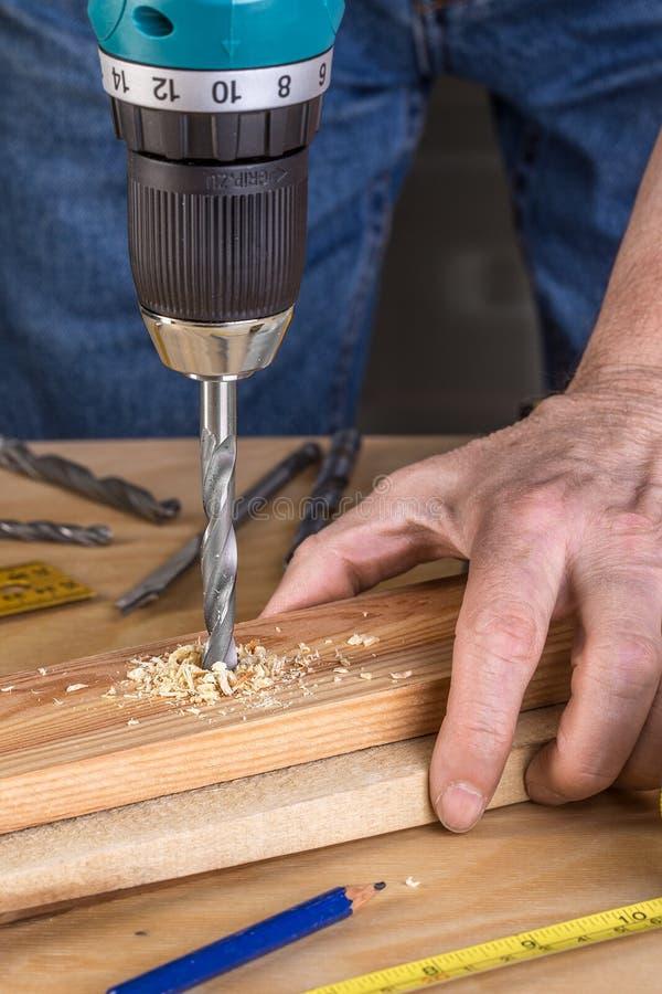 Bois de forage de charpentier utilisant la foreuse portative photographie stock
