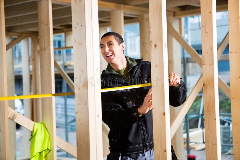 Bois de Laughing While Measuring de charpentier au chantier de construction photo stock