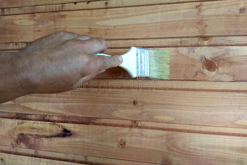 Bois de peinture de main de travailleur, bois protecteur pour des influences extérieures, désagrégation, insectes et champignon image libre de droits