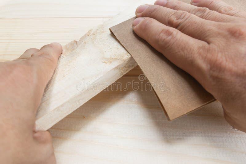 Bois de polissage de papier sablé d'homme de travailleur photos libres de droits
