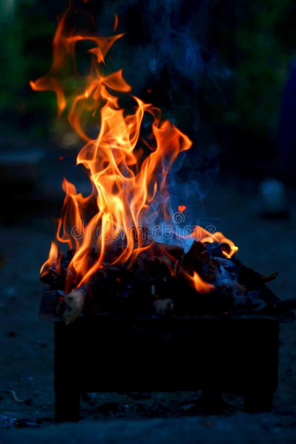 Bois et le feu brûlants sur le barbecue photographie stock