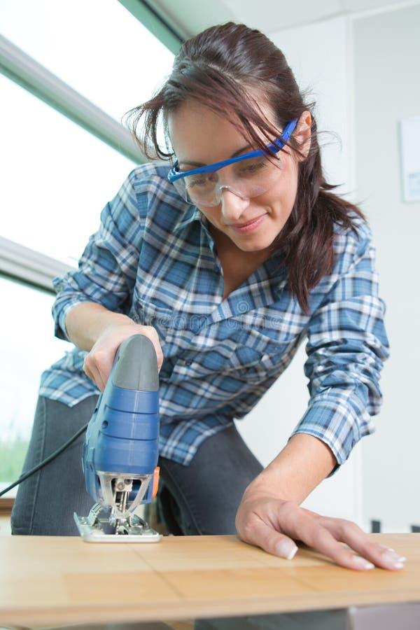 Bois femelle de coupe de charpentier dans l'atelier image stock